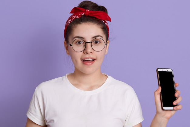 Yong hübsche frau, die isoliert über fliederraum mit aufregung steht, telefon hält, freizeitkleidung und brille trägt