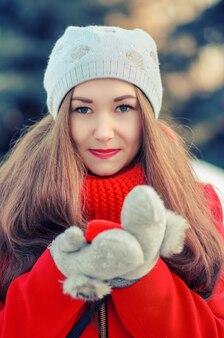 Yong lächeln mädchen mit langen haaren in einem roten mantel und schal mit dem geschenk in einer roten box. winterporträt im freien.