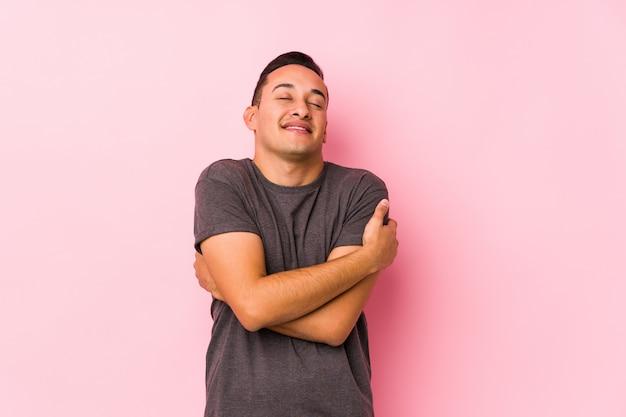 Yooung lateinischer mann, der in rosa wallhugs aufwirft, sorglos und glücklich lächelt.