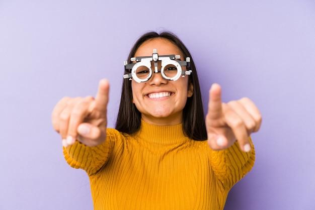Youn indische frau mit optometrie brille fröhliches lächeln zeigt nach vorne.