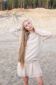 Youn kaukasisches mädchen mit langen haaren und nacktem make-up, das draußen aufwirft