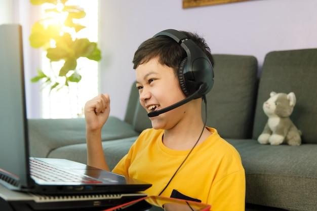 Youn kleiner süßer asiatischer 10er-junge mit kopfhörern, der im wohnzimmer zu hause sitzt, einen laptop-notebook-computer für online-fernstudium verwendet und aufgeregt und selbstbewusst den faustschlag erhebt