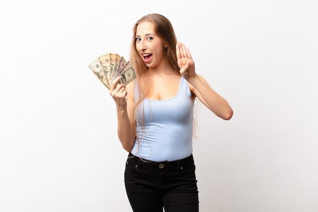 Yound blonde frau lächelt und sieht freundlich aus, zeigt nummer vier oder vierten mit der hand nach vorne, countdown hält dollar-banknoten