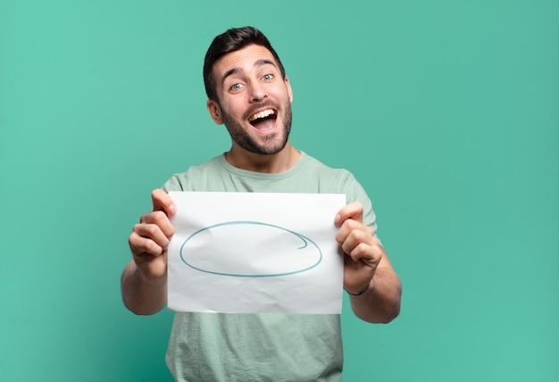 Younf gutaussehender mann, der ein blatt papier mit einem kopierraum hält