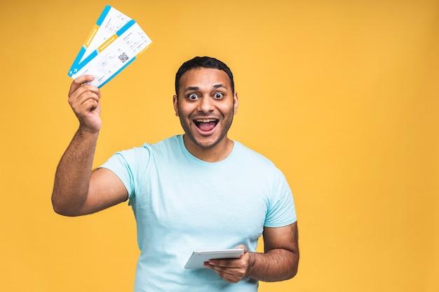 Young african american indian black man holding boarding pass tickets auf gelbem hintergrund isoliert. tablet-computer verwenden.