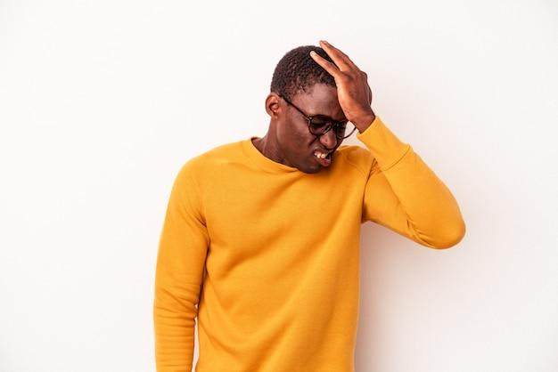 Young african american mann isoliert auf weißem hintergrund etwas vergessen, stirn mit handfläche schlagen und augen schließen.