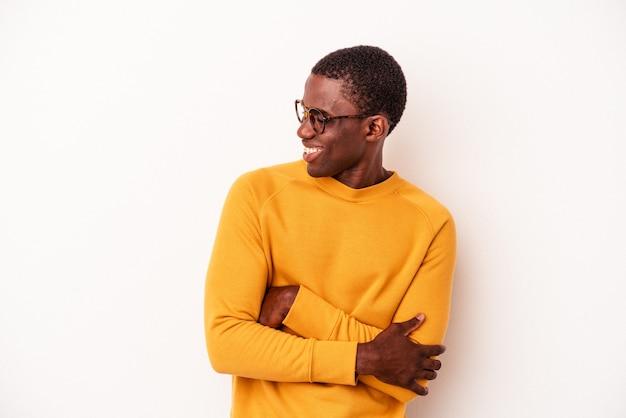 Young african american mann isoliert auf weißem hintergrund lächelnd zuversichtlich mit verschränkten armen.