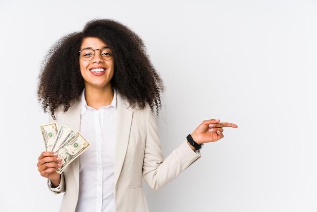 Young afro business woman holding ein kredit-auto isoliert young afro business woman holding ein kredit-carsmiling und beiseite zeigen, zeigt etwas an der leerstelle.
