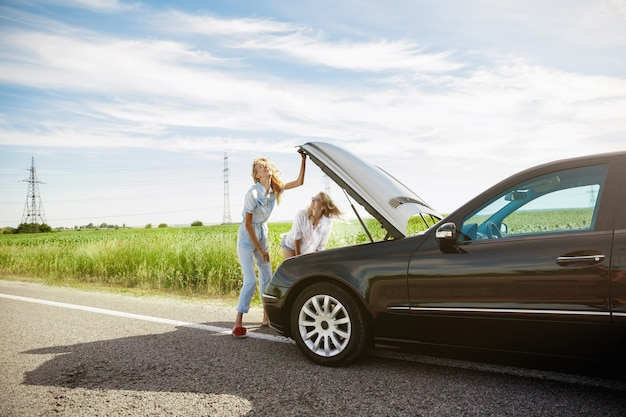Youngcouple fährt an einem sonnigen tag mit dem auto in den urlaub
