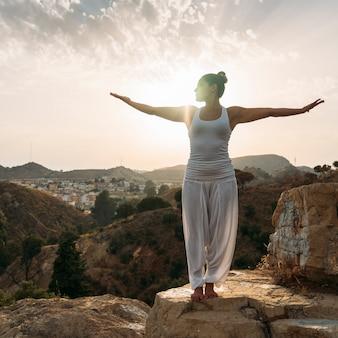 Youngwoman, yoga, natur und sonnenuntergang