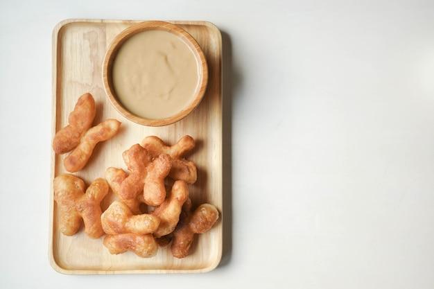 Youtiao oder cakwe mit milkteapudding auf braunem hölzernem hintergrund.