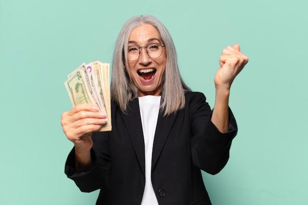 Ysenior hübsche geschäftsfrau mit dollarbanknoten. geldkonzept