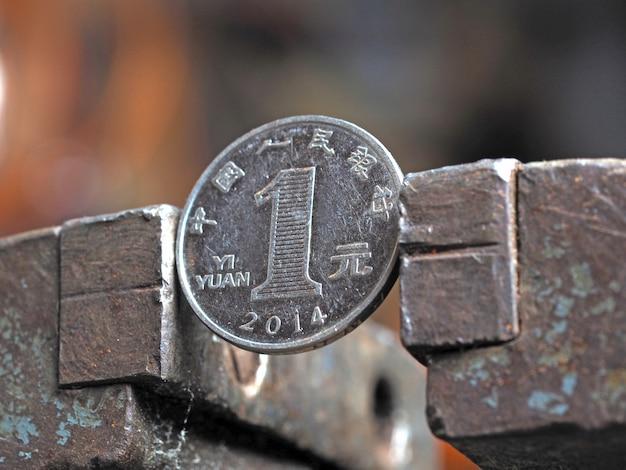 Yuan-münze in einem metallschraubstock festgeklemmt