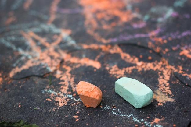 Ywo kleine grüne und orangefarbene kreide auf einer bürgersteigoberfläche nahaufnahme
