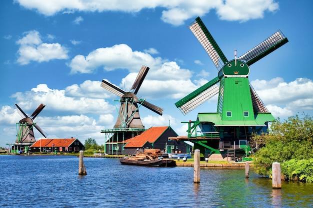 Zaanse schans, niederlande - circa august 2020: holländische windmühle in grüner landschaft in der nähe von amsterdam, mit blauem himmel und flusswasser.