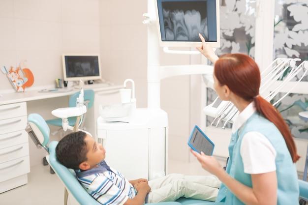 Zähne auf dem bildschirm. rothaariger kinderzahnarzt, der dem kleinen jungen ein röntgenbild der zähne auf dem bildschirm zeigt