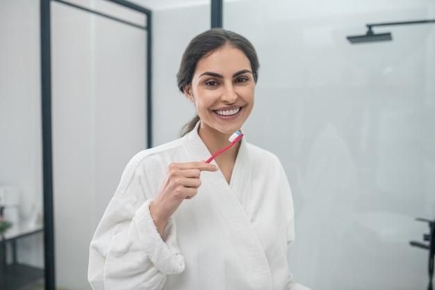 Zähne putzen. eine junge hübsche frau in einem weißen bademantel beim zähneputzen