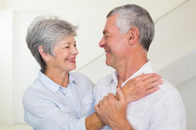 Zärtlich pensionierte paare, die an einander lächeln