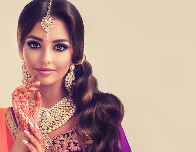 Zärtlicher blick und sanftes lächeln auf dem gesicht der jungen frau, gekleidet in indische nationaltracht
