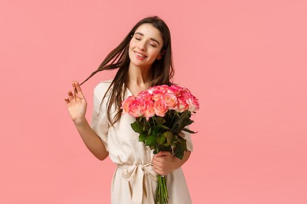 Zärtlichkeit, freude und valentinstag konzept. charmante, schöne und sinnliche brünette frau im kleid, rollende locken auf dem haar glücklich augen schließen und träumen, blumenlieferung erhalten, rosen halten