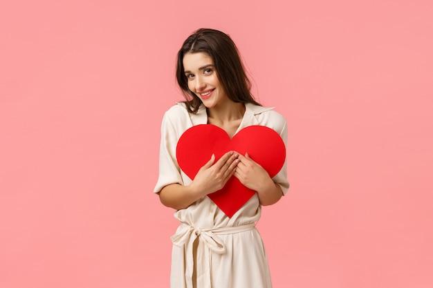 Zärtlichkeit, romantik und pflegekonzept. attraktives dummes mädchen im kleid, herzkarte umarmend, valentinszeichen und kokette blickkamera haltend, lächelnd entzückt
