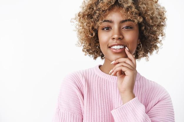 Zärtlichkeit, schönheit und lifestyle-konzept. porträt einer gut aussehenden sinnlichen und selbstbewussten afroamerikanischen frau, die die lippe berührt, verführerisch lächelt selbstbewusst und selbstbewusst in die kamera schaut