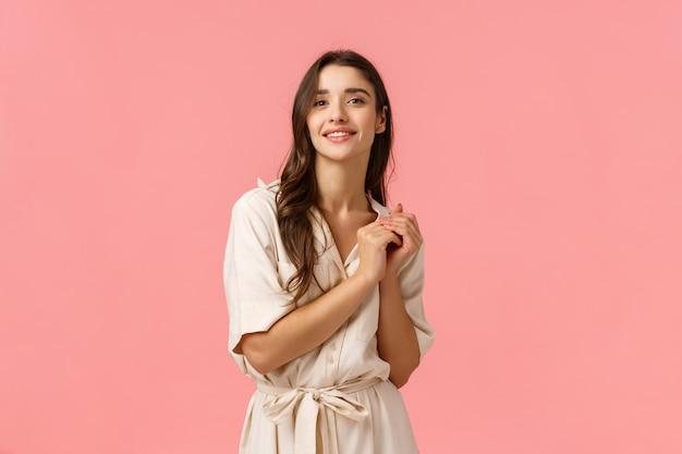 Zärtlichkeit, schönheit und modekonzept. charmante zarte junge kaukasische frau im kleid, berührende hände, die sinnlich lächeln und mit verträumtem blick, stehende rosa wand betrachten