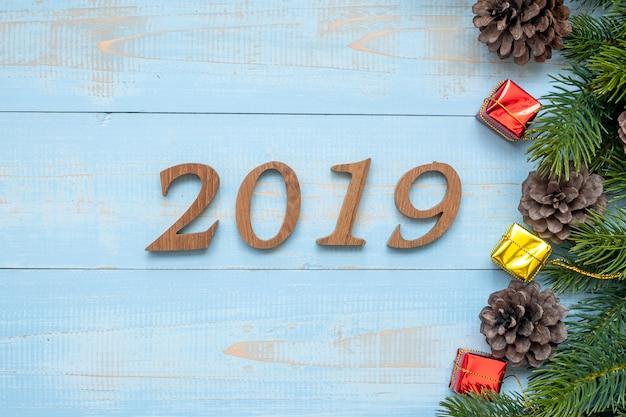 Zahl 2019 mit weihnachtsdekorationen auf hölzernem hintergrund