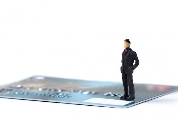 Zahl miniaturgeschäftsmann, der auf kreditkarte steht