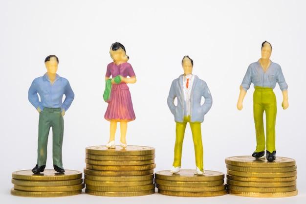 Zahl miniaturgeschäftsmann, der auf münzenstapel steht