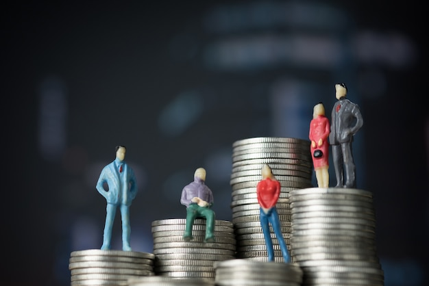 Zahl miniaturgeschäftsmann, der auf stapel der münze steht