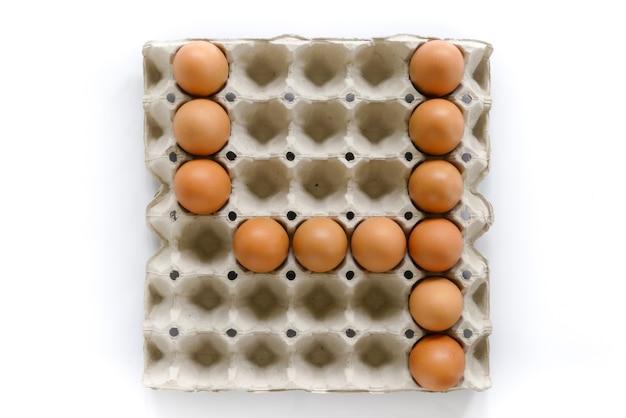 Zahlbuchstaben vereinbaren von den eiern im papierbehälter auf weißem hintergrund.