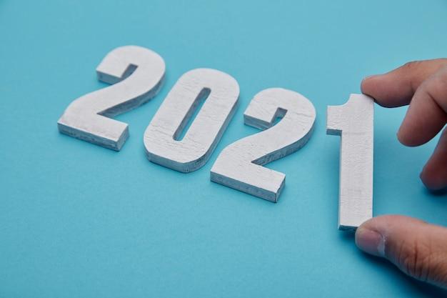 Zahlen 2021 und hand auf pastellblauem hintergrund für neujahr