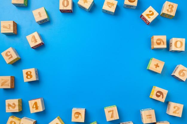 Zahlen. hölzerne bunte alphabetblöcke auf blauem hintergrund, ebenenlage, draufsicht.