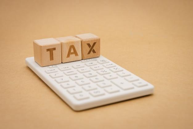 Zahlen sie das jährliche einkommen (tax) für das jahr mit dem taschenrechner. verwenden als hintergrundgeschäftskonzept