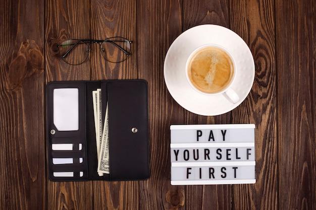 Zahlen sie sich zuerst. persönliches finanzkonzept. lederbrieftasche auf einem holztisch.