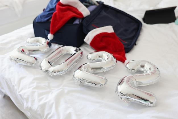 Zahlen und gesammelter koffer mit sachen mit weihnachtsmannmützen liegen auf dem bett