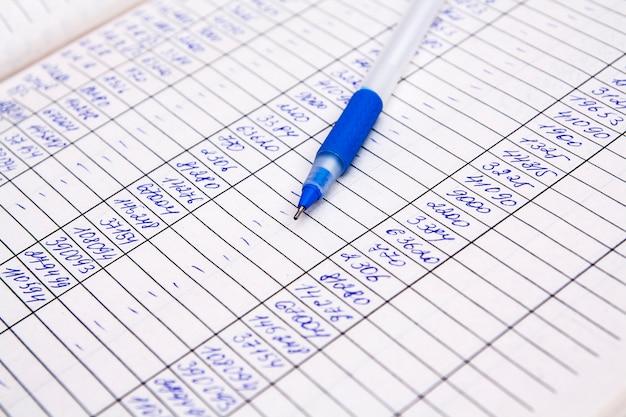 Zahlen und stift schließen fragment eines dokuments mit jahresabschluss. konzeptbilanz, rechnungen