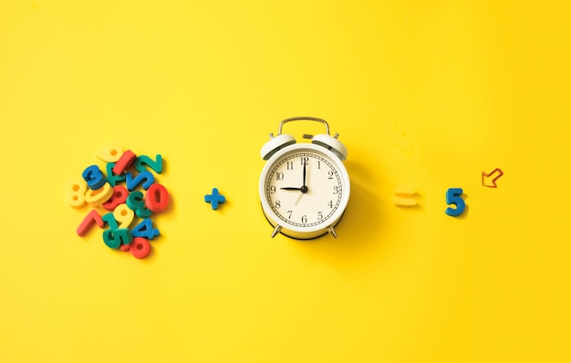 Zahlen und wecker auf einem gelben bunten tisch. unterricht und erziehung, unterrichten von kindern in mathematik