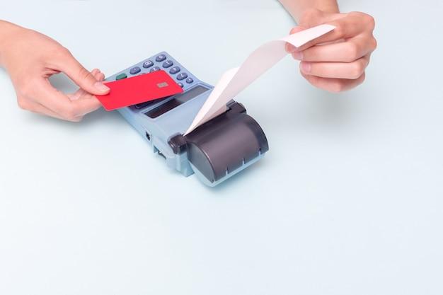 Zahlung für einkäufe per kreditkarte. nahaufnahme einer hand mit einer bankkarte und einer hand mit einem scheck, quittung auf einer registrierkasse auf blauem hintergrund. geschäftskonzept, einzelhandel, online-verkauf