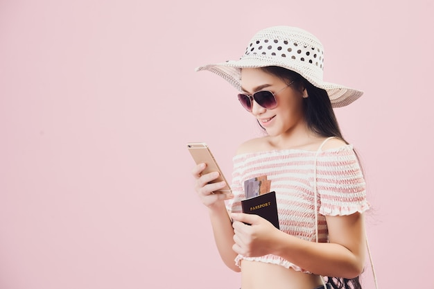Zahlung für online-shopping., frau fröhlich beim online-shopping per smartphone und kreditkarte im studio rosa hintergrund. pastellrosa-tonfilter.