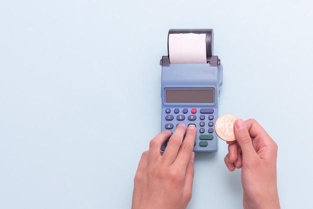 Zahlung mit elektronischem geld eine hand mit einer bitcoin-münze und handzählung an der kasse
