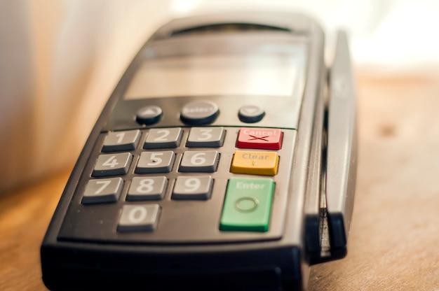 Zahlung mit kreditkarte - kaufmann hält pos terminal. zahlen