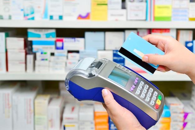 Zahlung mit kreditkarte und terminal auf vielen medikamentenregalen in apotheken