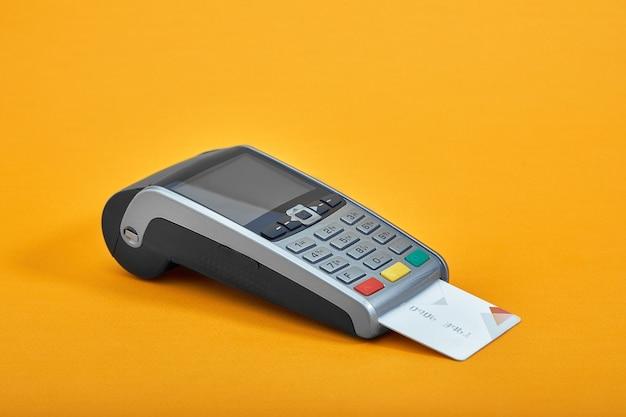 Zahlung per kreditkarte. terminal auf gelbem oberflächenkopierplatz.