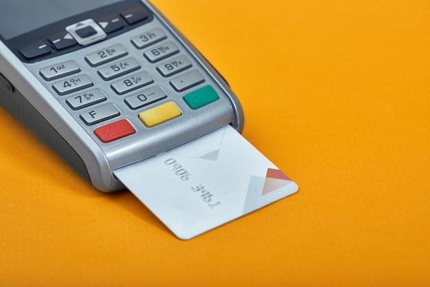 Zahlung per kreditkarte. terminal auf gelbem tischkopierplatz.