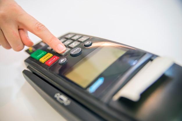 Zahlungskarte in einem bankterminal. das konzept der elektronischen zahlung. hand-pin-code auf pin-pad von karte maschine oder pos-terminal gute foto