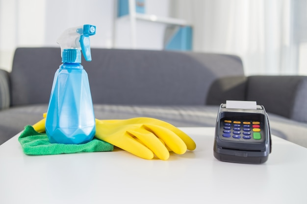 Zahlungsterminal neben sprühflasche und gummihandschuhen