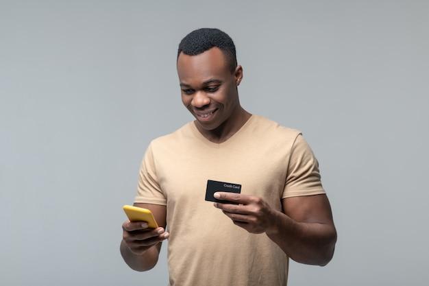 Zahlungsvorgang. lächelnder junger erwachsener afroamerikanischer mann mit smartphone und bankkarte in den händen, der vor hellem hintergrund steht