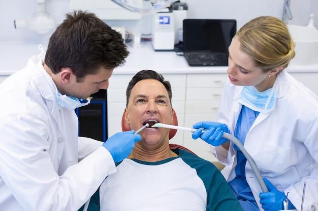 Zahnärzte, die einen männlichen patienten mit werkzeugen untersuchen
